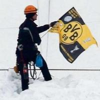 Фен развя флага на Борусия на покрива на стадиона на Шалке